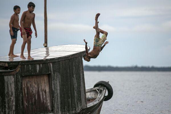 Un bambino si tuffa nell'acqua nella baia di Melgaco, a sud-ovest dell'isola di Marajo, Brasile, il 29 maggio 2020 - Sputnik Italia