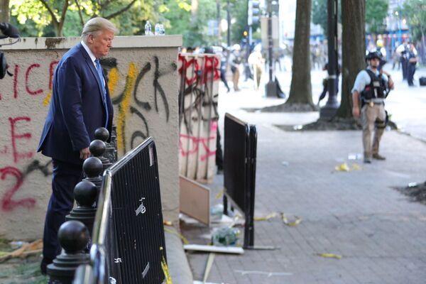 Il presidente Donald Trump vicino ad un edificio con i graffiti dei manifestanti di fronte alla Casa Bianca durante le proteste in corso a seguito della morte di George Floyd a Minneapolis, USA - Sputnik Italia