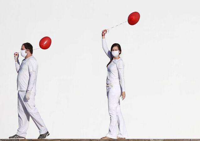 Gli artisti si esibiscono con palloncini rossi in una protesta in onore delle persone morte per malattia di coronavirus (COVID-19), Brasile