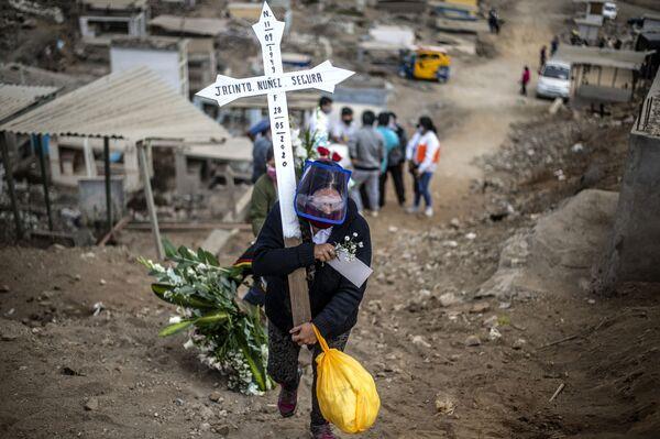 Un parente di una vittima di coronavirus porta una croce al cimitero di Lima, Perù - Sputnik Italia