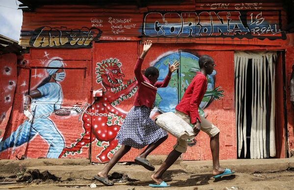 I bambini corrono lungo una strada davanti a un murale che avverte le persone dei pericoli del nuovo coronavirus, nella baraccopoli di Kibera, Kenya, mercoledì 3 giugno 2020 - Sputnik Italia