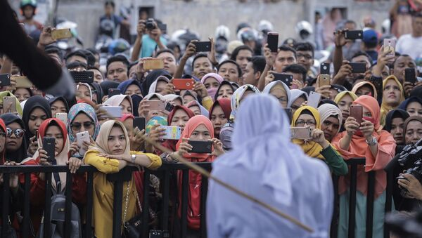 People use their mobile phones to take pictures as a Shariah law official whips a woman who is convicted of prostitution during a public caning outside a mosque in Banda Aceh, Indonesia, Friday, April 20, 2018. Indonesia's deeply conservative Aceh province on Friday caned several unmarried couples for showing affection in public and two women for prostitution before an enthusiastic audience of hundreds. The canings were possibly the last to be carried out before large crowds in Aceh after the province's governor announced earlier this month that the punishments would be moved indoors - Sputnik Italia