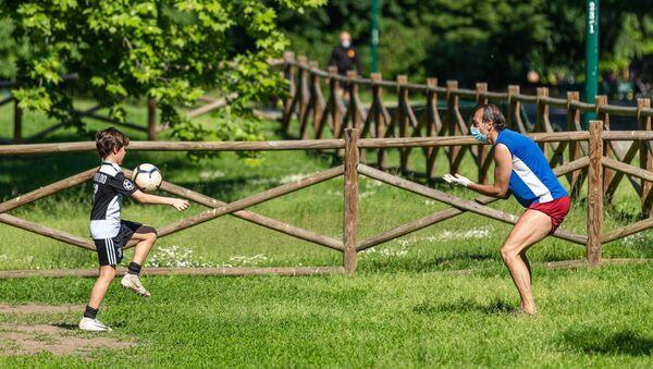 Papa e figlio giocano a pallone in un parco  - Sputnik Italia