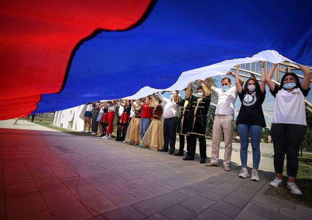 I partecipanti alle celebrazioni del Giorno della Russia con la bandiera russa nel Parco dell'Amicizia della città di Georgievsk, territorio di Stavropol, Russia