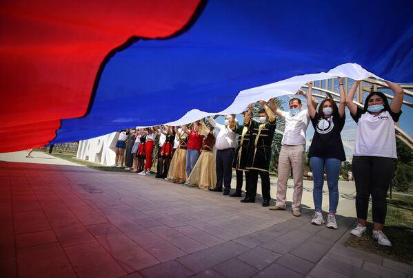 I partecipanti alle celebrazioni del Giorno della Russia con la bandiera russa nel Parco dell'Amicizia della città di Georgievsk, territorio di Stavropol, Russia - Sputnik Italia