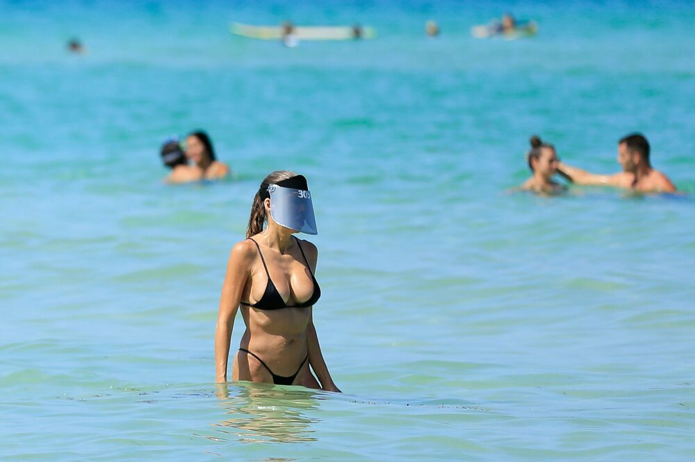 Una donna indossa una visiera protettiva mentre si gode l'oceano a South Beach il 10 giugno 2020 a Miami Beach, in Florida