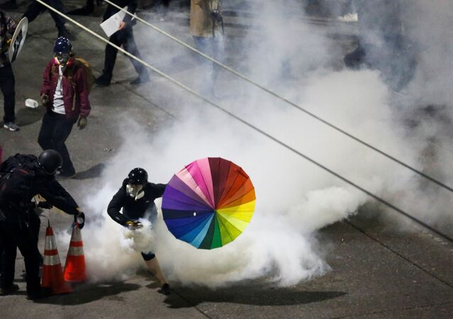 A protester with a rainbow umbrella picks up a gas canister as law enforcement deploys chemical agents and blast balls during a protest against racial inequality in the aftermath of the death in Minneapolis police custody of George Floyd, near the Seattle Police department's East Precinct in Seattle, Washington, U.S. June 8, 2020.