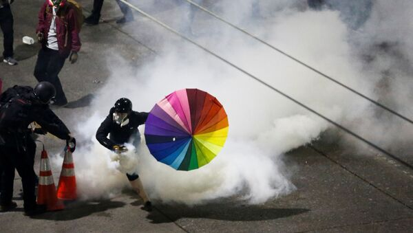 A protester with a rainbow umbrella picks up a gas canister as law enforcement deploys chemical agents and blast balls during a protest against racial inequality in the aftermath of the death in Minneapolis police custody of George Floyd, near the Seattle Police department's East Precinct in Seattle, Washington, U.S. June 8, 2020.  - Sputnik Italia