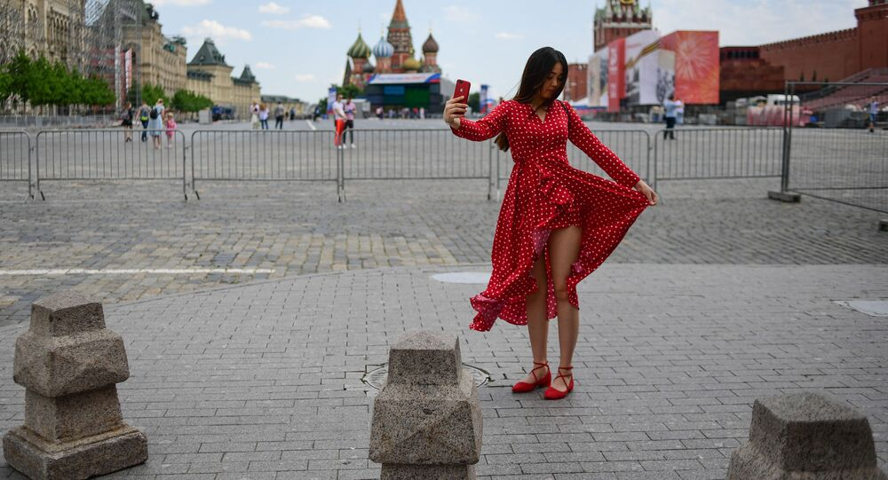 A woman poses for a selfie at Red Square on a sunny day amid coronavirus outbreak, in Moscow, Russia.