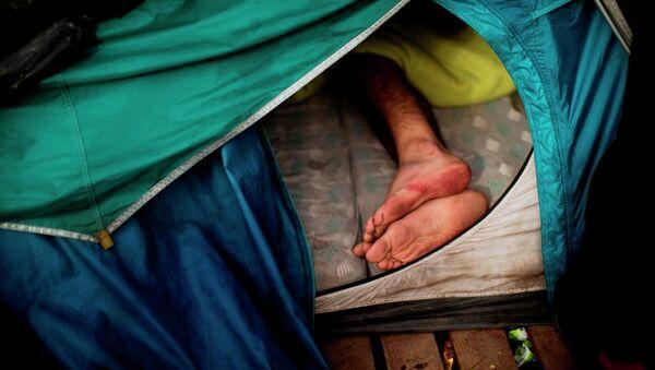 Un migrante dorme in una tenda vicino a Calais, Francia. - Sputnik Italia