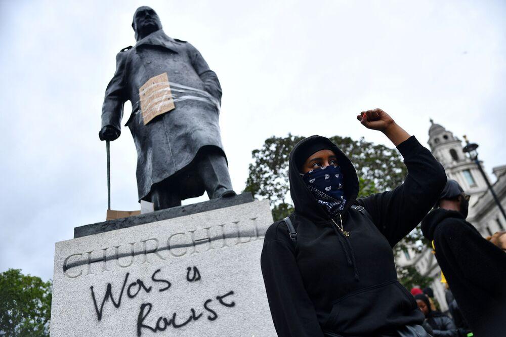 Un manifestante davanti ai graffiti su una statua di Winston Churchill durante una protesta di Black Lives Matter a Londra, il 7 giugno 2020