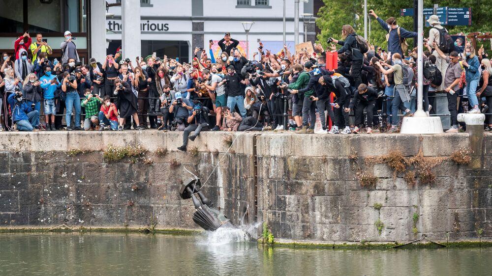 La statua del commerciante di schiavi del 17° secolo Edward Colston cade in acqua dopo che i manifestanti l'hanno abbattuta durante una protesta contro la disuguaglianza razziale a seguito della morte di George Floyd a Minneapolis, Bristol, Gran Bretagna, il 7 giugno 2020
