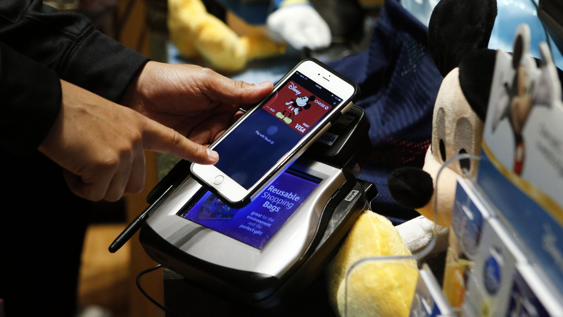 Un uomo fa un acquisto al Disney Store a New York con l'Apple Pay di iPhone - Sputnik Italia, 1920, 15.03.2021