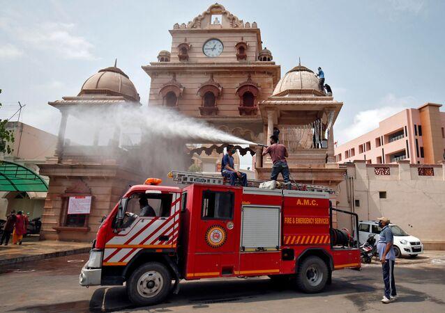 Pompieri spruzzano disinfettante nel tempio di Lord Jagannath temple, dopo l'alleggerimento delle restrizioni del lockdownm voluto dalle autorito, imposto per rallentare la diffusione del COVID-19 , in Ahmedabad, India, Giugno15, 2020. REUTERS/Amit Dave