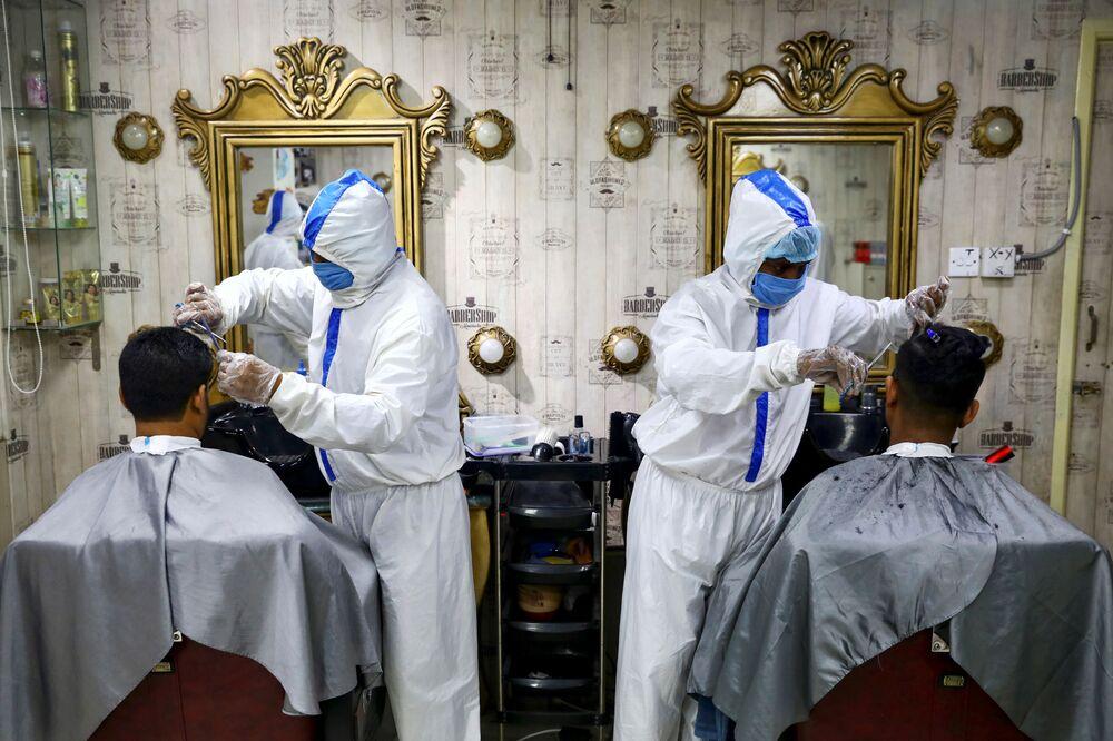 Barbieri che indossano tute protettive e mascherine con i clienti a Dhaka, Bangladesh, il 16 giugno 2020