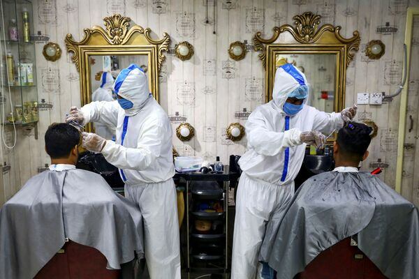Barbieri che indossano tute protettive e mascherine con i clienti a Dhaka, Bangladesh, il 16 giugno 2020 - Sputnik Italia