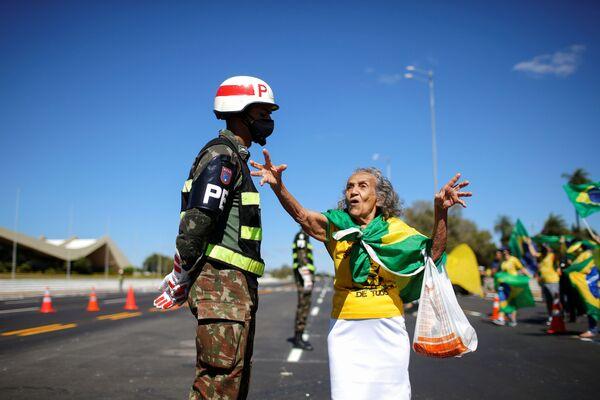 Un sostenitore del presidente brasiliano Jair Bolsonaro parla con un soldato brasiliano durante una protesta contro il Tribunale federale supremo del paese, di fronte al quartier generale dell'esercito a Brasilia, in Brasile, il 14 giugno 2020 - Sputnik Italia
