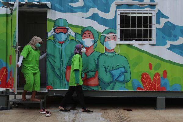 Gli operatori sanitari escono da un laboratorio mobile prima di analizzare i tamponi raccolti durante i test di coronavirus di massa a Jakarta, Indonesia, giovedì 18 giugno 2020 - Sputnik Italia