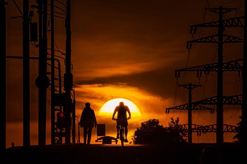 Un uomo va in bicicletta al tramonto a Mosca