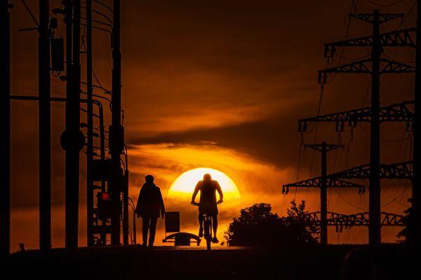 Un uomo va in bicicletta al tramonto a Mosca - Sputnik Italia