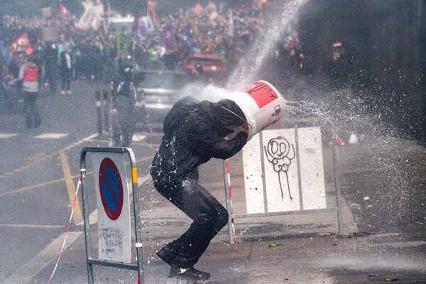 Un manifestante si protegge mentre viene colpito da un cannone ad acqua dalla polizia di fronte a una prefettura regionale durante una manifestazione a Nantes il 16 giugno 2020 nell'ambito di una giornata nazionale di proteste per chiedere migliori condizioni di lavoro agli operatori sanitari - Sputnik Italia