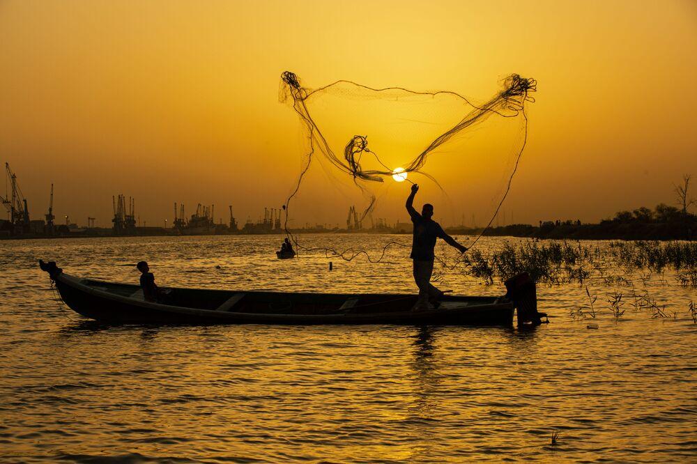 Un pescatore al tramonto nella città irachena meridionale di Bassora il 12 giugno 2020