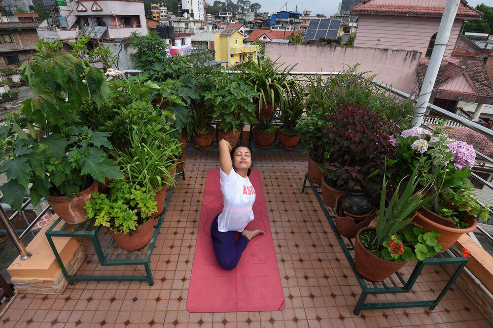 L'istruttore di yoga Suzana Pradhan si esercita sul tetto della sua casa a Kathmandu durante la Giornata internazionale dello yoga