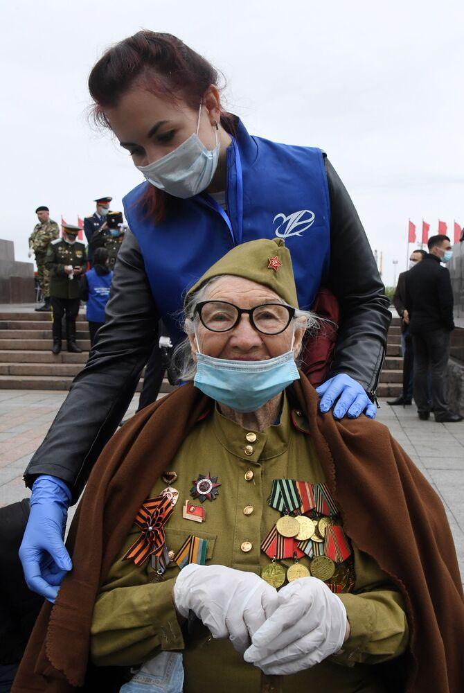 Un veterano della Seconda Guerra Mondiale e un volontario in mascherina durante la parata per il 75esimo anniversario della Vittoria contro il nazismo a Vladivostok.