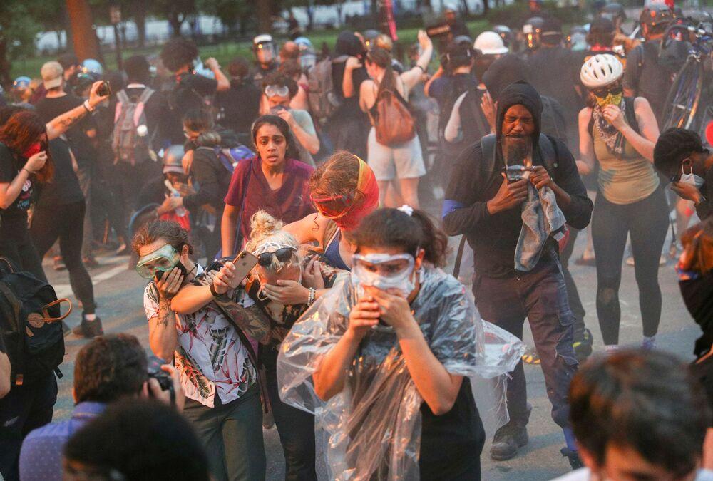 I manifestanti scappano dalla polizia durante le proteste contro la disuguaglianza razziale a Washington, USA.