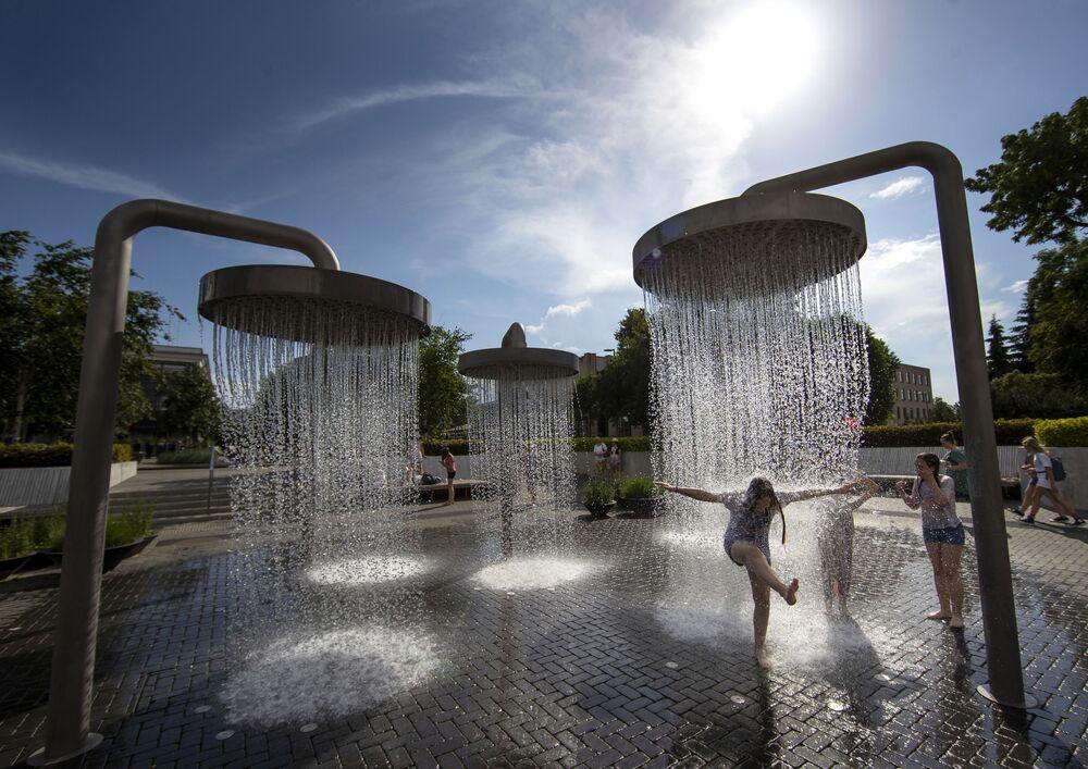Bambini giocano nelle fontane durante l'afa a Vilnius, Lituania.