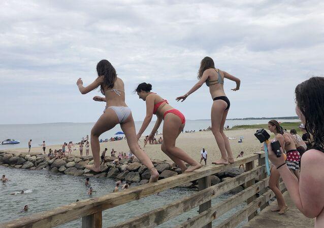 Delle ragazze si tuffano da un ponte a Edgartown, Massachusetts, USA.