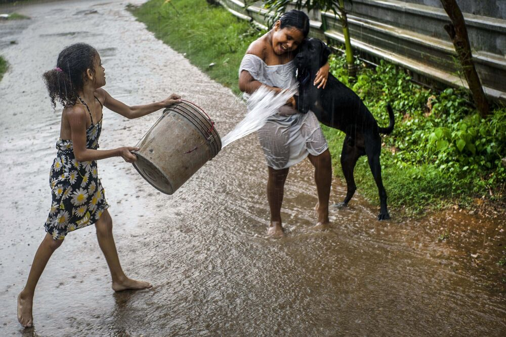 Bambini giocano sotto la pioggia all'Avana, Cuba.
