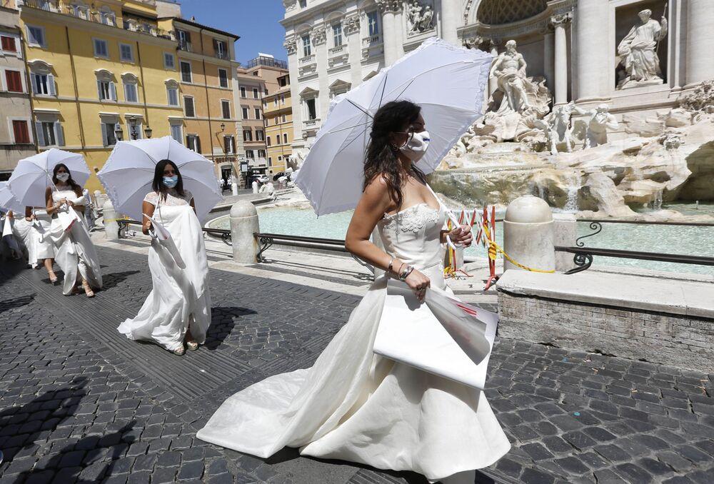 Abiti bianchi e cartelli di protesta per il rinvio forzato dei loro matrimoni.