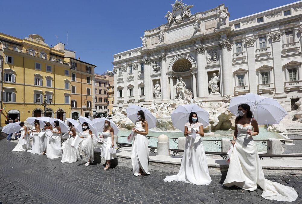 Una decina di spose tutte in bianco, con un ombrellino per ripararsi dal sole e la marcia nuziale in sottofondo hanno inscenato un flash mob davanti alla Fontana di Trevi e poi a Montecitorio