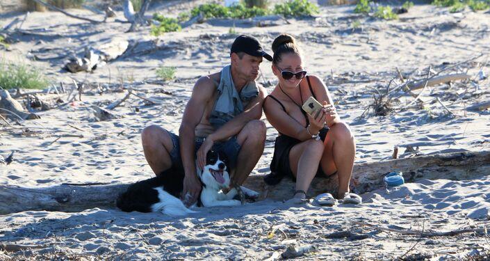 Una coppia con cane sulla spiaggia in Italia