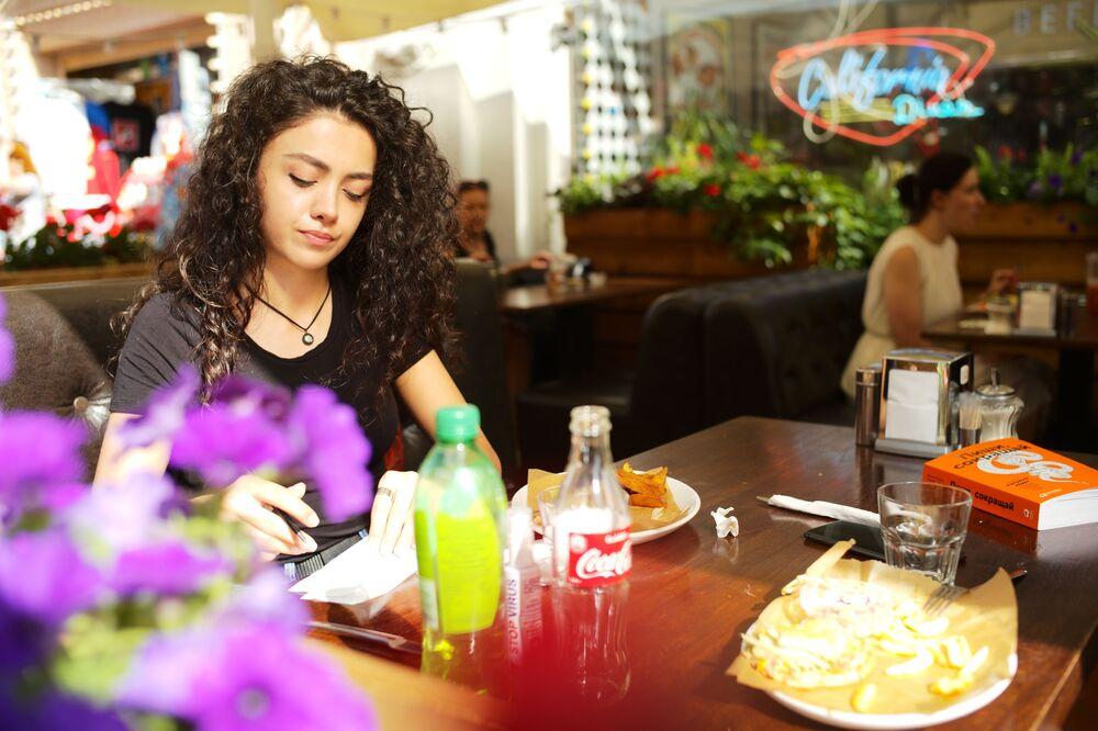 Una ragazza si rilassa in un bar sulla Vecchia Arbat dopo la fine della quarantena a Mosca.