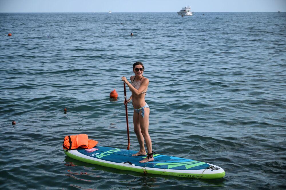 Una ragazza va su un SUP nei pressi di una spiaggia a Sochi.