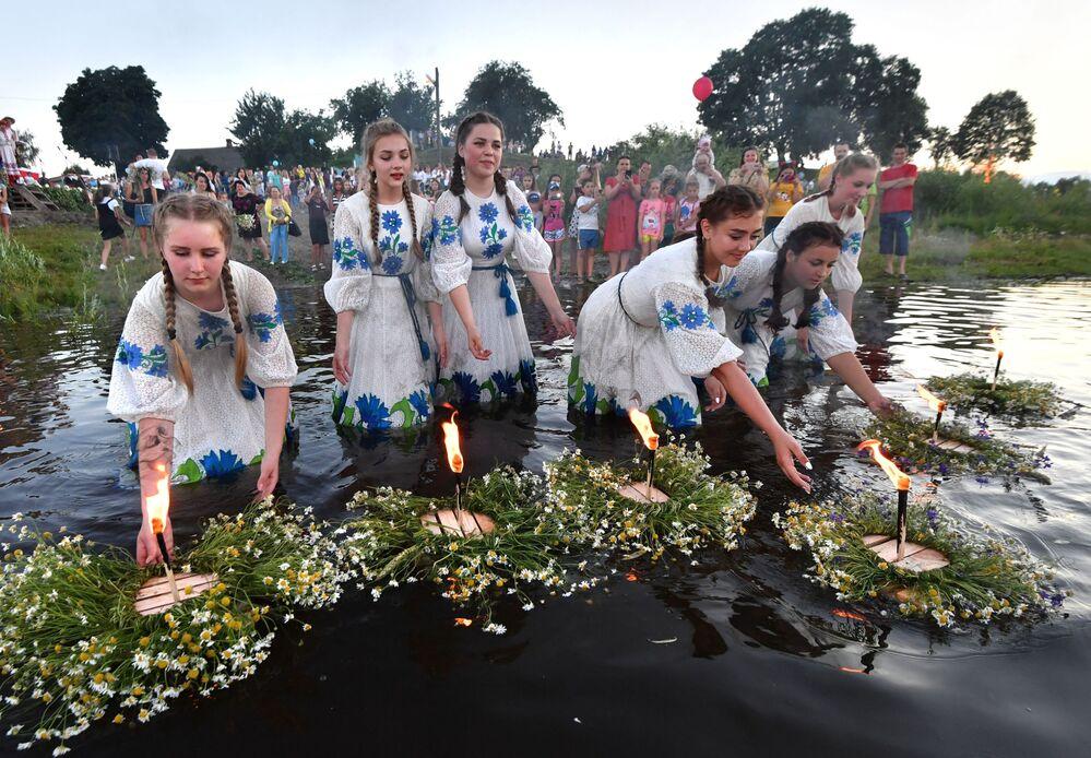 Ragazze mettono corone di fiori sull'acqua durante la festa di Ivan Kupala (San Giovanni in versione slava) sulla riva del fiume Pripyat nell'antica città bielorussa di Turov.