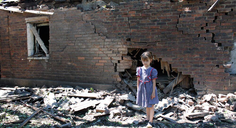 Bambina davanti a casa distrutta dai bombardamenti dell'esercito ucraino nel Donbass (foto d'archivio)