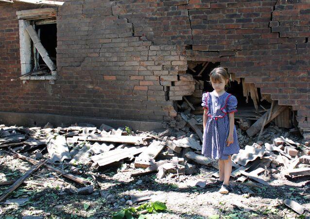 Una ragazzina davanti alla casa distrutta dai bombardamenti dell'esercito ucraino a Gorlovka, Donbass.