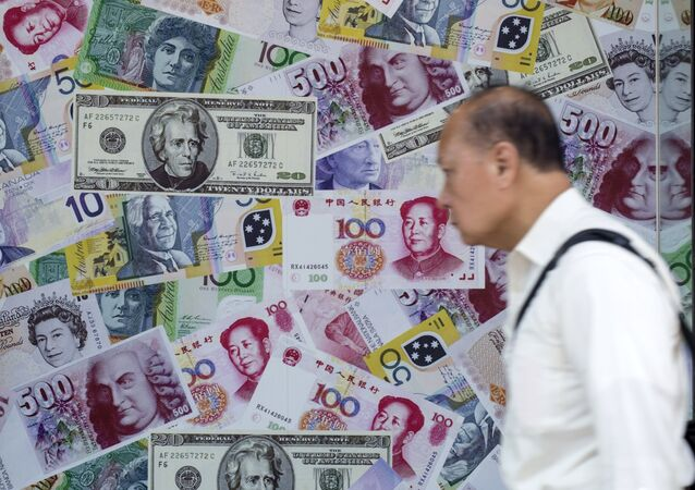 A man walks past an advertisement promoting China's renminbi (RMB) or yuan, U.S. dollar and Euro exchange services at foreign exchange store in Hong Kong, China, August 13, 2015
